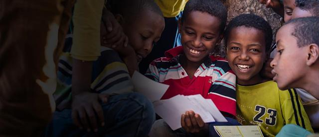 A smiling boy in a group of boys straining to read a letter from a sponsor
