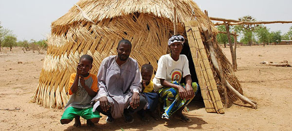A family sits outside of a straw hut