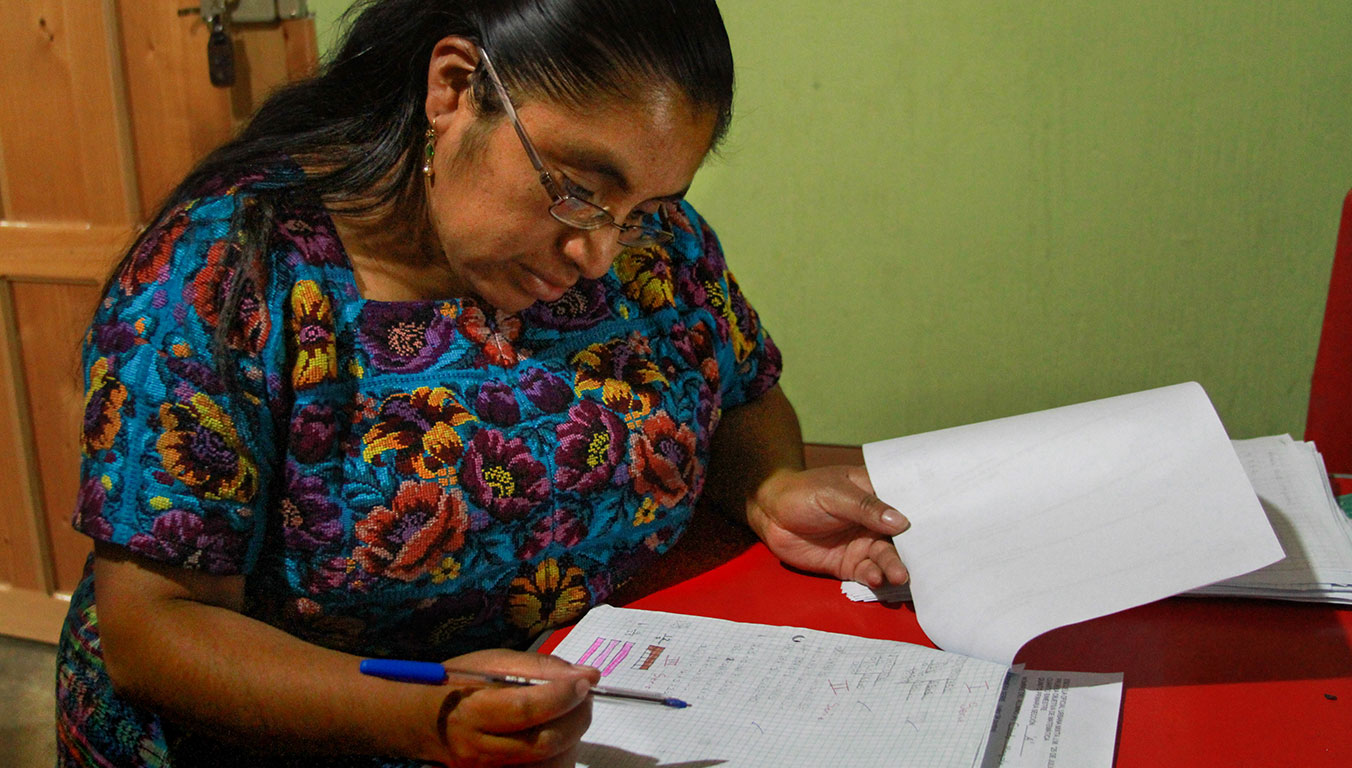 Blanca checks her students' work at her home in Guatemala