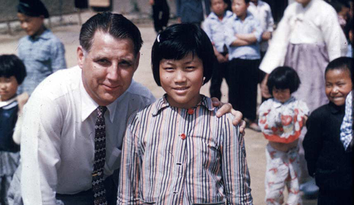 Everett Swanson smiles witha Korean child
