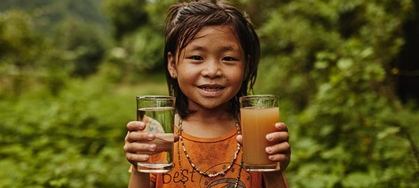 A girl in Indonesia proudly shows her clean drinking water