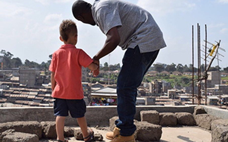 Kennedy and his son overlook the Mathare slums where he was born and raised