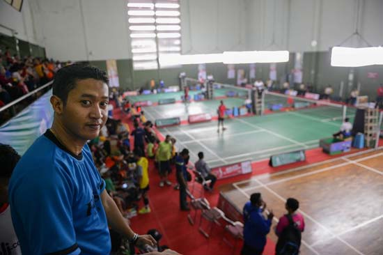 Fredy watches a badminton competition in Indonesia