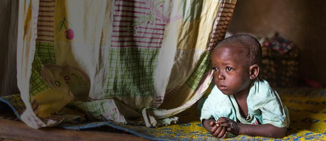 Child laying near fabric curtain and looking out