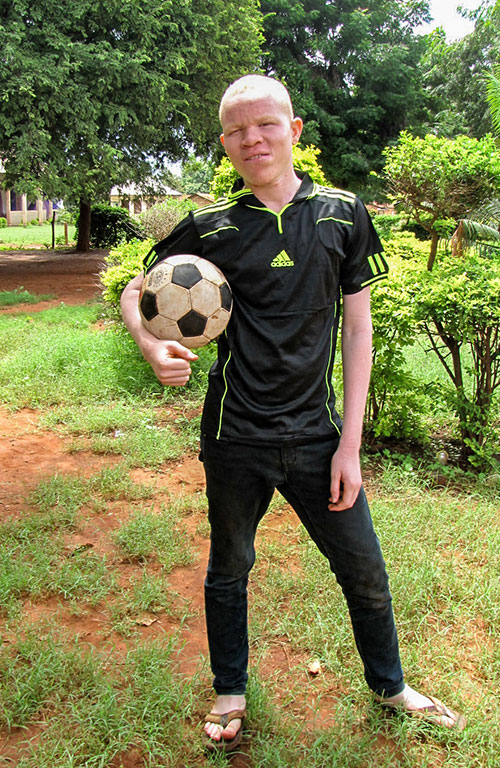 Yona holding a soccer ball for his team with the Compassion center