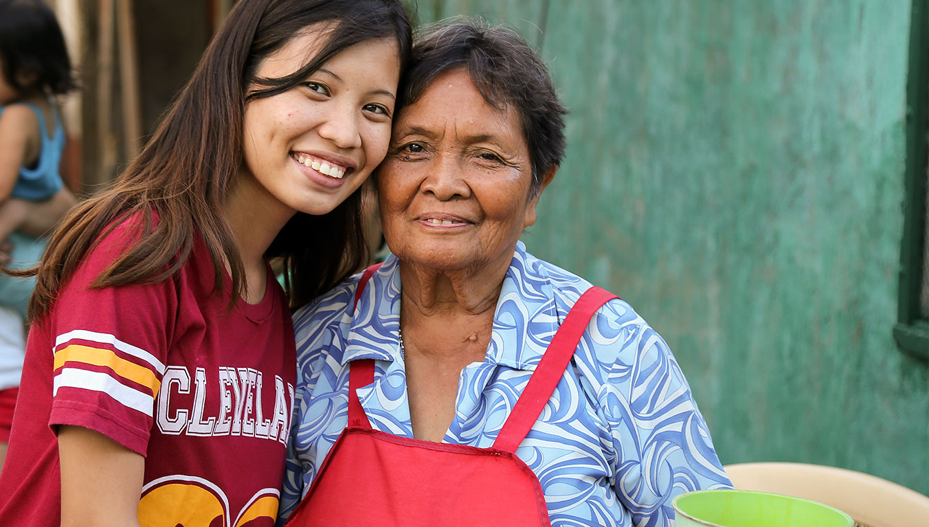 Angelyn with her grandmother outside their home in Cebu City.