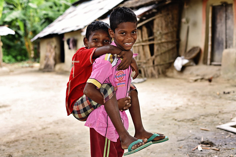 A young boy carries his brother on his back