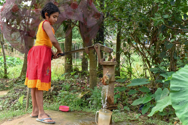A young girl wearing a colorful dress pumps water from a well