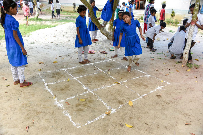 A group of children play a traditional game outside their child development center