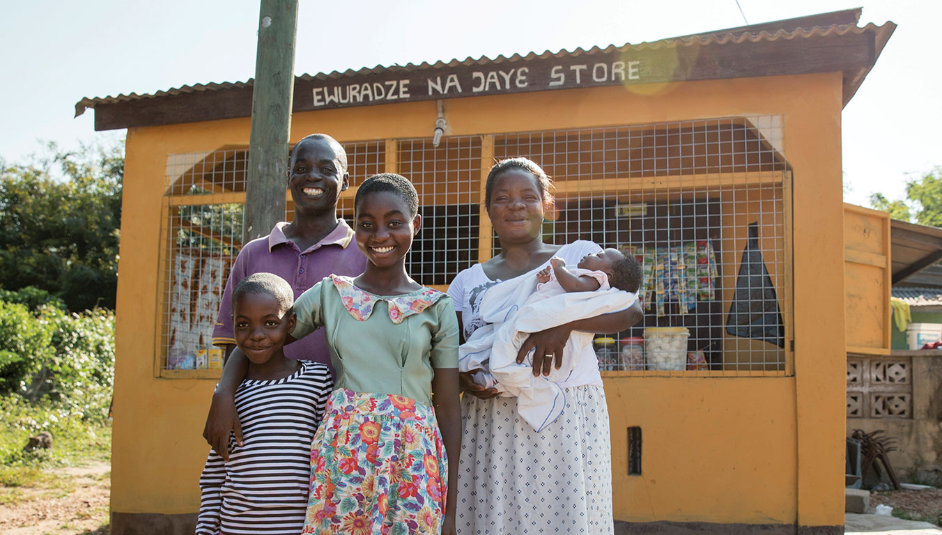 Benedicta and her family standing outside their grocery shop