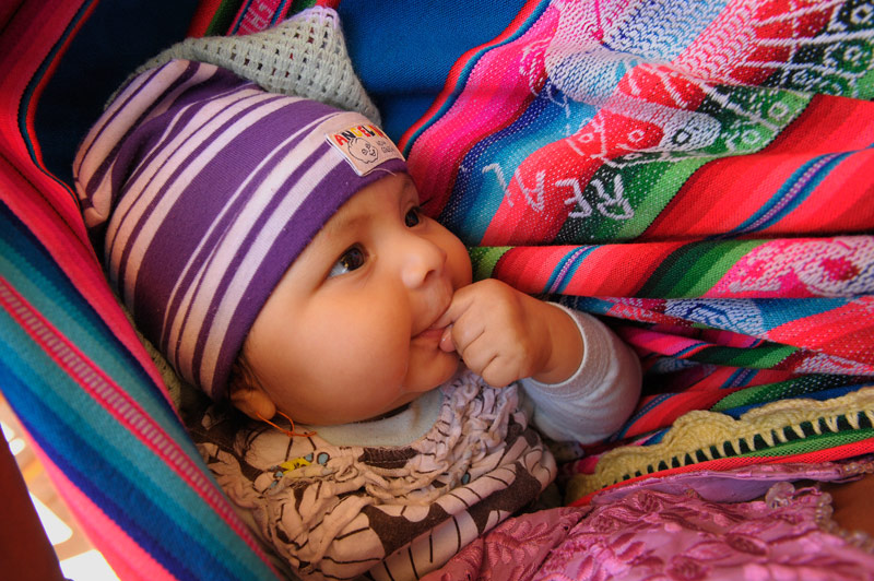 A Bolivian baby is wrapped in traditional, striped fabric
