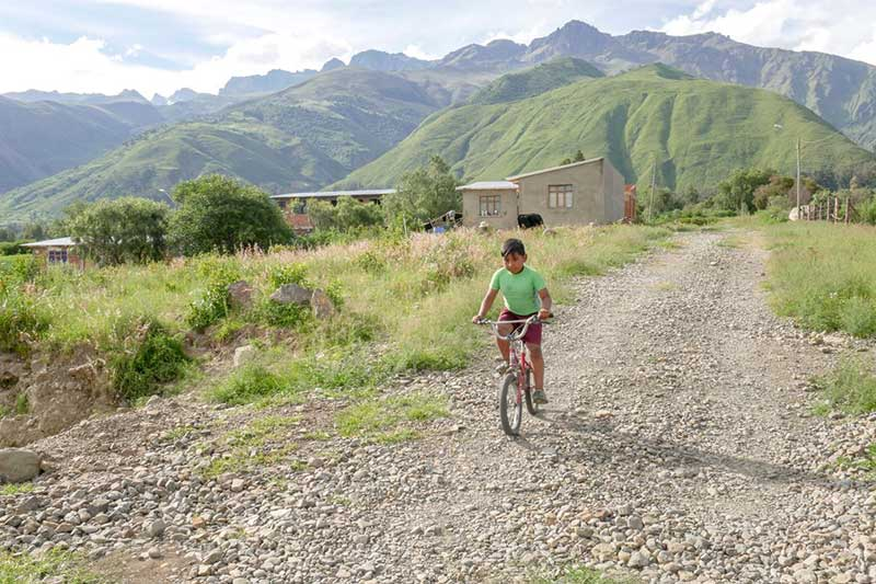 A boy rides a bicycle down a rocky path in Bolivia