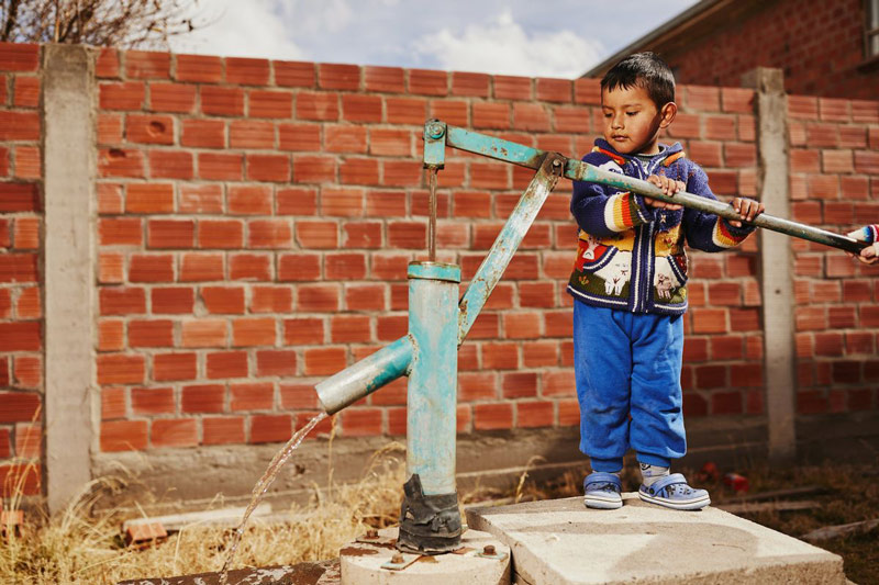 A young boy pumps water from a well