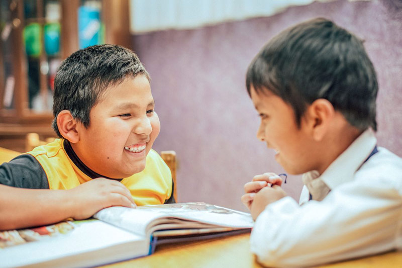 Two boys laugh and read the Bible together