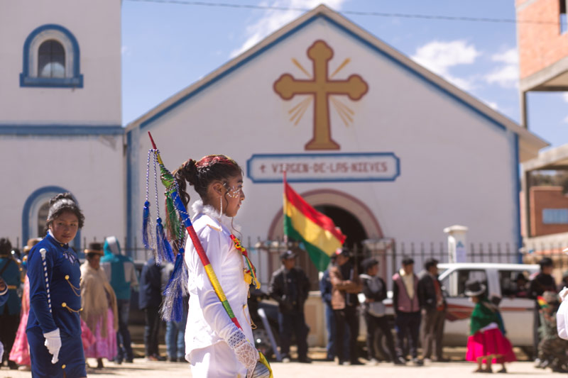 A girl walks as part of a parade in front of a church