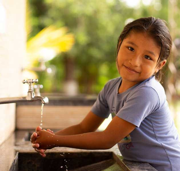 A girl cleaning her hands with safe water provided by the Compassion center