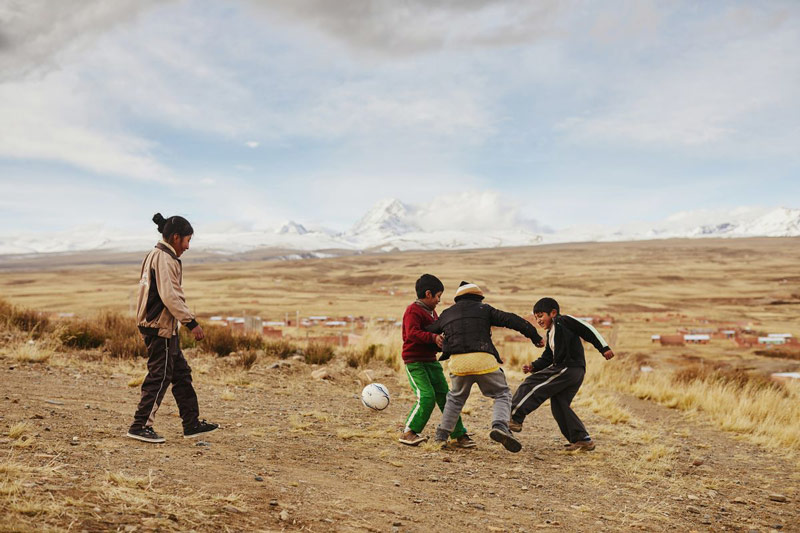 Children play soccer with snowcapped mountains in the distance