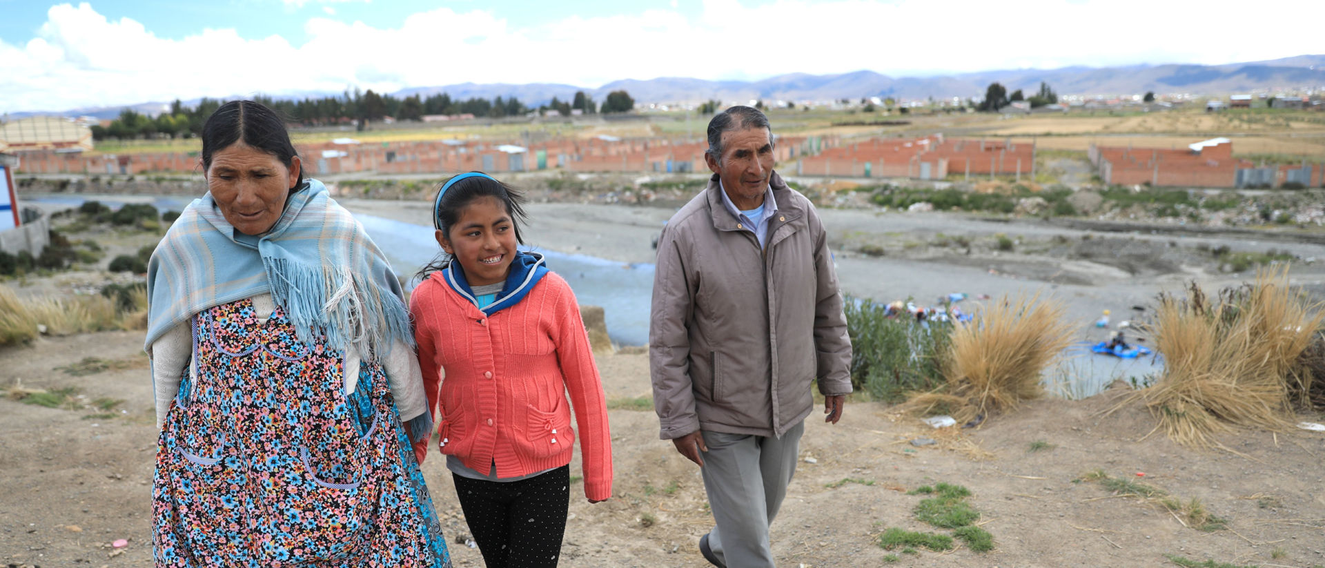 Nayely walks with her parents near the river where they and many other community members wash their clothes.