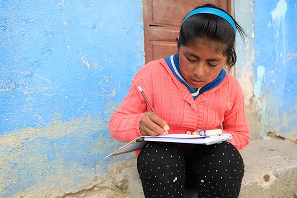 Nayely does school work outside her Compassion center.