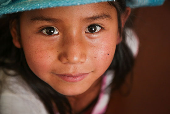 A Bolivian girl with rosy cheeks and a blue hat