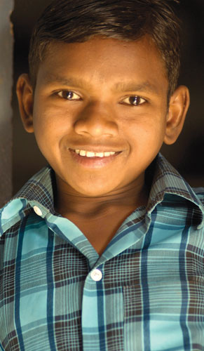 Boy with blue shirt smiling - World in Adversity