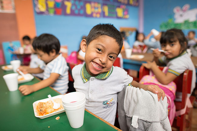 Boy smiling while eating lunch at school