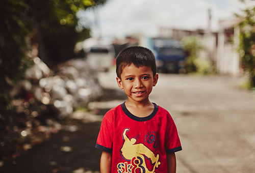 Boy with a red and gold shirt standing outside