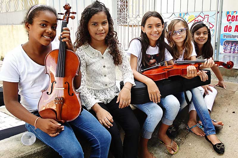 A group of girls hold musical instruments at their child development center