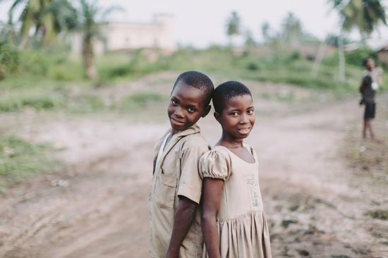 A boy and girl standing back to back smiling