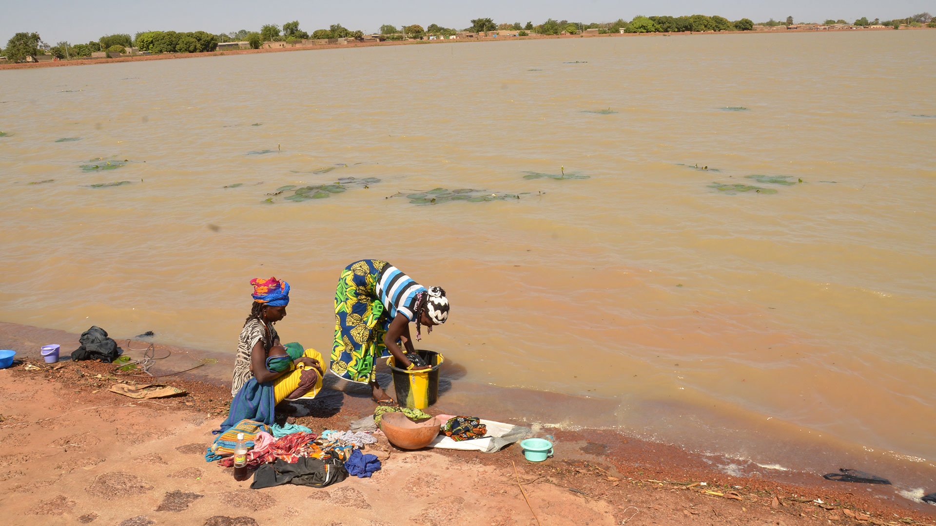 Women wash clothes in a polluted lake in Burkina Faso