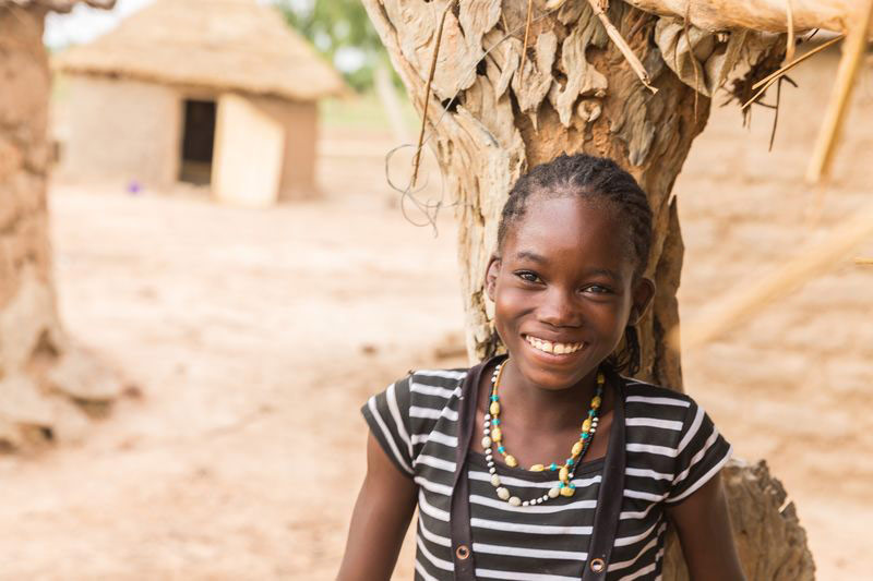 A girl smiles while leaning against a tree in her neighborhood