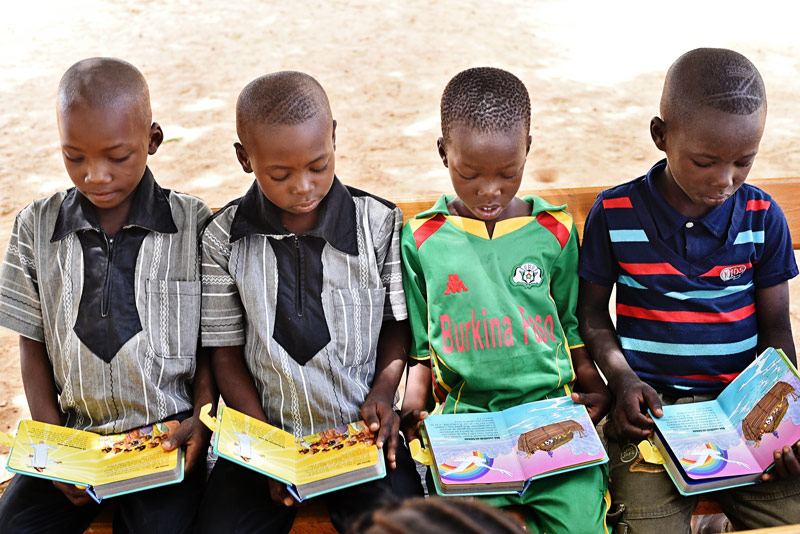 Little boys read their first Bibles together