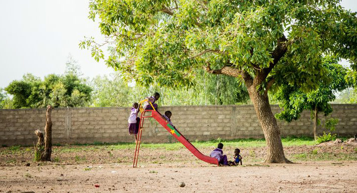 Children play on a slide outside their child development center
