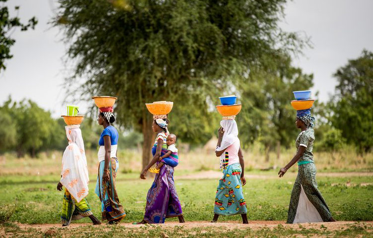 Women carry large bowls of milk on their heads to sell at the market