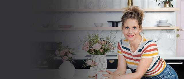 Candace Cameron Burre standing at a kitchen island and smiling