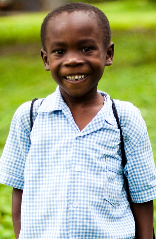 A Haitian boy wearing a blue checkered shirt smiling