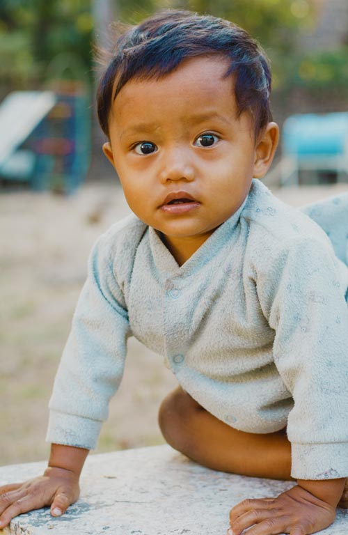 A toddler from Thailand playing outside