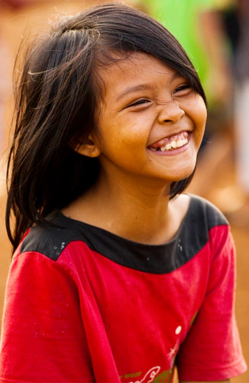A young girl wearing a red top smiling