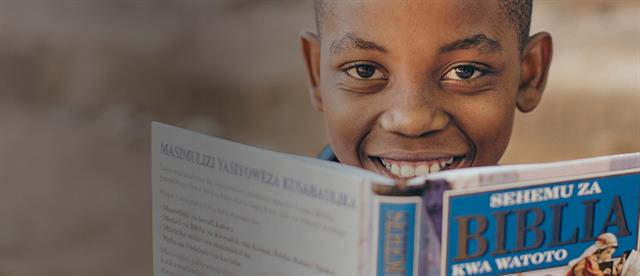 A boy peeks over the top of a Bible he is holding open
