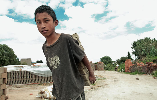 A boy in a gray t-shirt carries a stack of bricks on his back