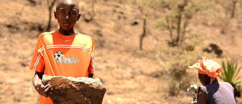 A teenager in an orange shirt is carrying a large rock