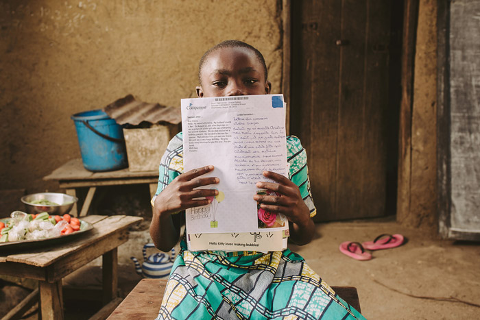 A child holds up a letter from a sponsor
