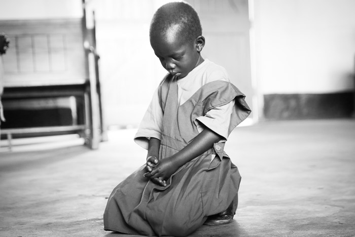A child kneels and prays