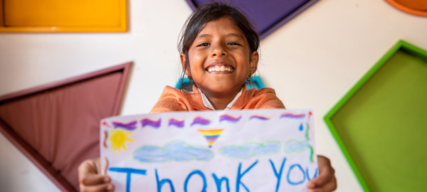 A child with thank you sign