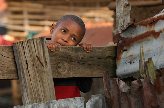 A young Tanzanian boy wearing a red jacket is peering over a fence that is built near rusty corrugated metal siding