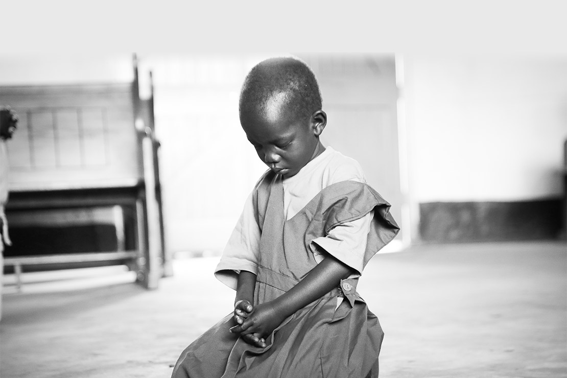 A young child kneels and prays