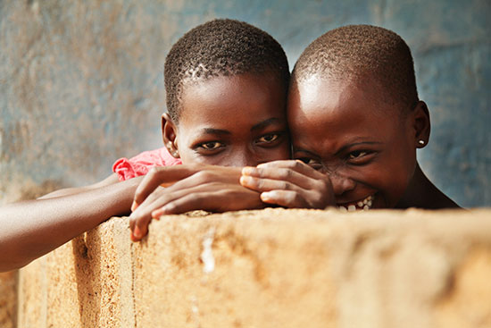 Two Ghanian children peek their eyes over a low cement wall