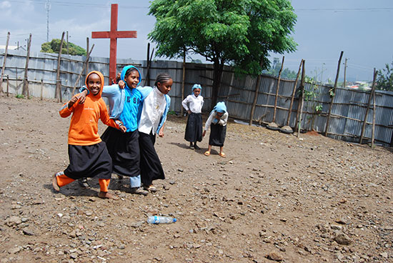 Ethiopian children walking across a dirt field. A cross is in the background.