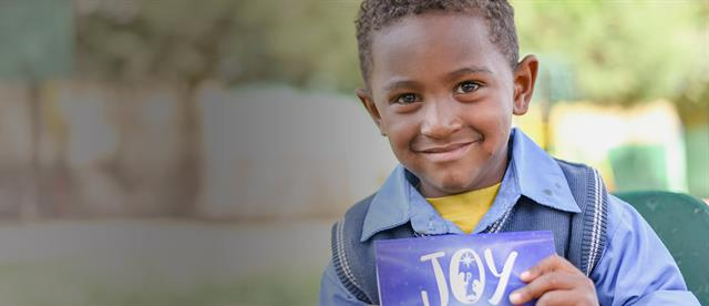 A boy holding a card with the word joy written on it