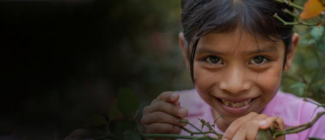 A young girl smiling while picking flowers